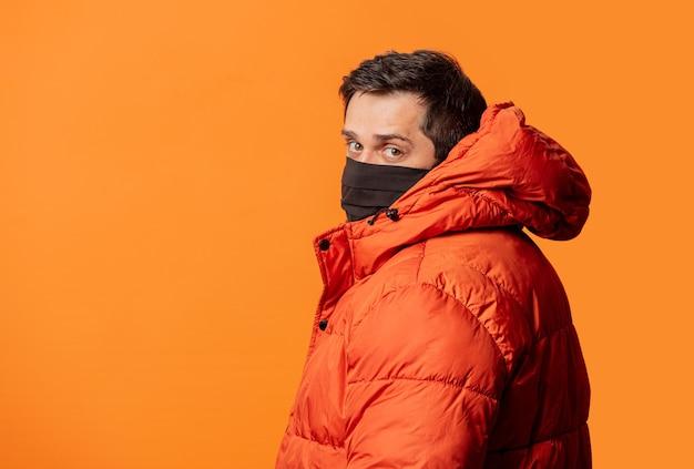 Kerl in gesichtsmaske und daunenjacke auf orange