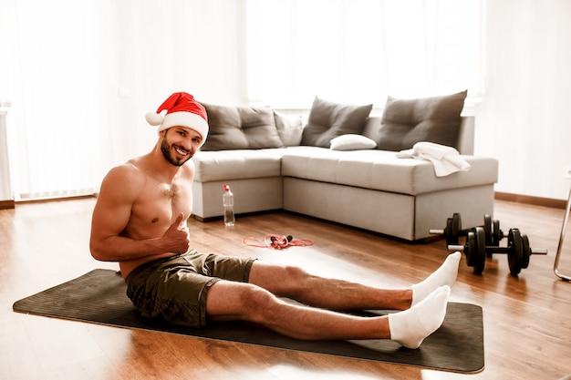 Kerl in weihnachtsmanns rotem weihnachtshut beim training zu hause