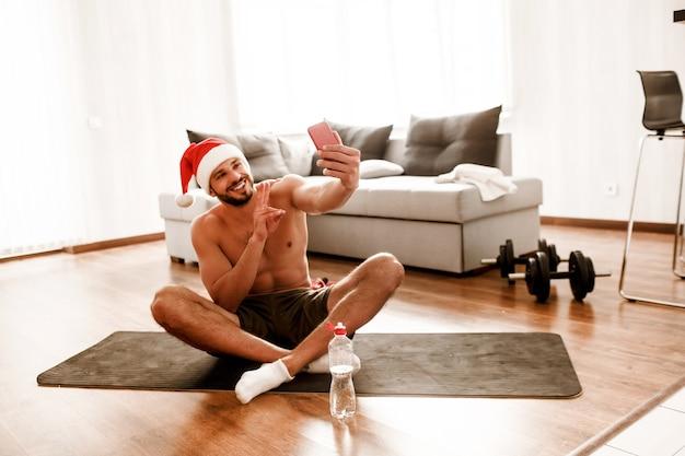 Kerl in weihnachtsmanns weihnachtsrothut, der selfie nimmt