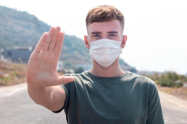 Kerl, junger mann in der schützenden sterilen medizinischen maske auf seinem gesicht betrachten kamera draußen, auf asiatischer straßenshowpalme, hand, stoppen sie kein zeichen. luftverschmutzung, virus, pandemie coronavirus-konzept. covid-19