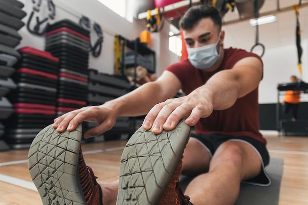 Kerl macht stretching im fitnessstudio mit maske