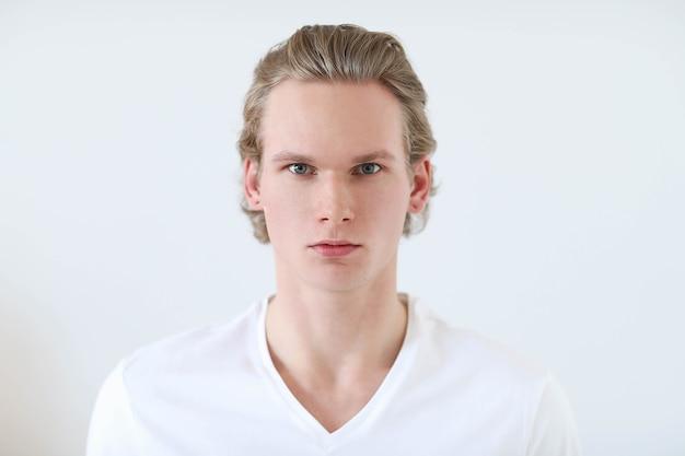 Kerl mit blonden haaren und weißem hemd