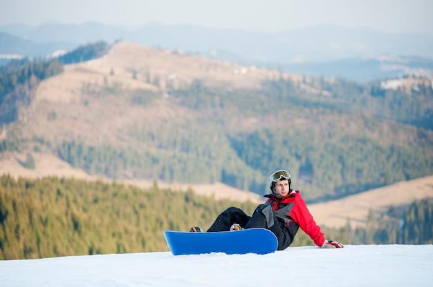 Kerl mit dem snowboard, der auf schneebedeckter steigung auf einen berg sitzt und weg schaut