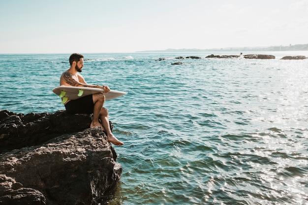 Kerl mit dem surfbrett, das auf felsen nahe meer sitzt