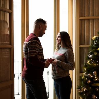 Kerl mit der geschenkbox, die dame nahe fenster und weihnachtsbaum betrachtet