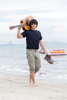 Kerl mit der gitarre, die auf dem strand, frachthose steht