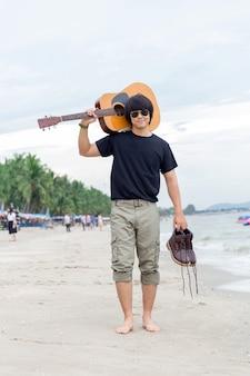 Kerl mit der gitarre, die auf dem strand, frachthosen steht