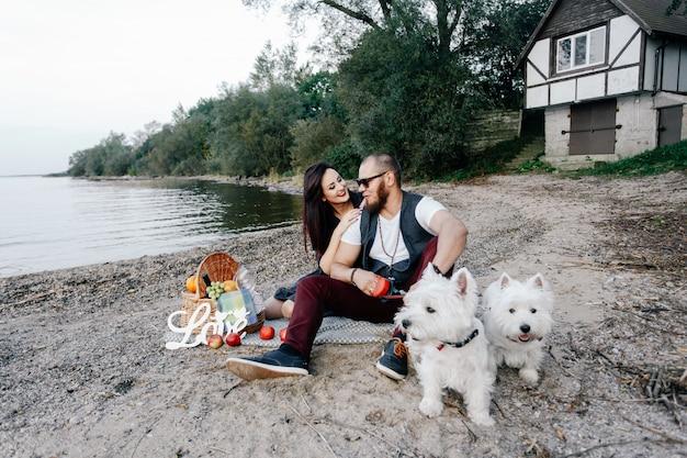 Kerl mit einem mädchen kam zu einem picknick mit zwei welpen