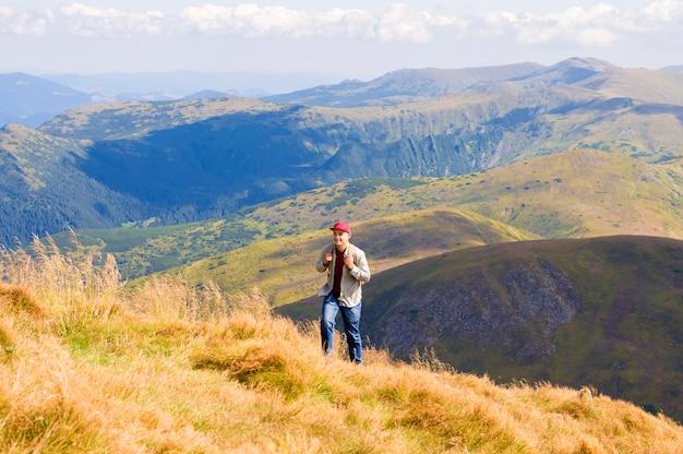 Kerl mit einem rucksack reist in die berge