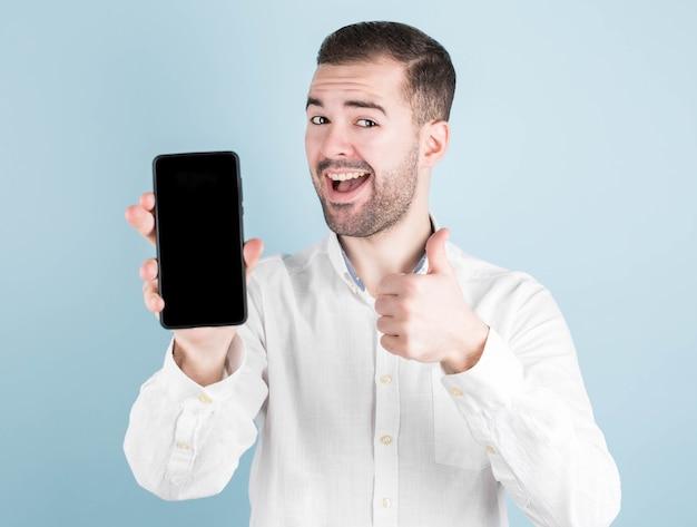 Kerl mit einem telefon zeigt superzeichen, getönten, kopierraum