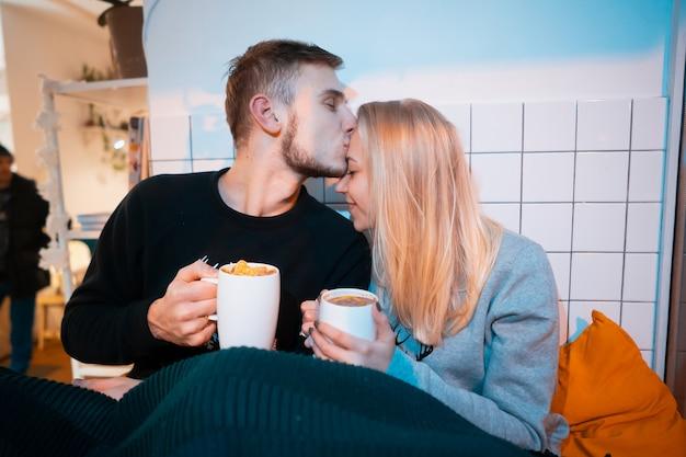 Kerl mit einer jungen frau, die heißen kaffee und tee trinkt