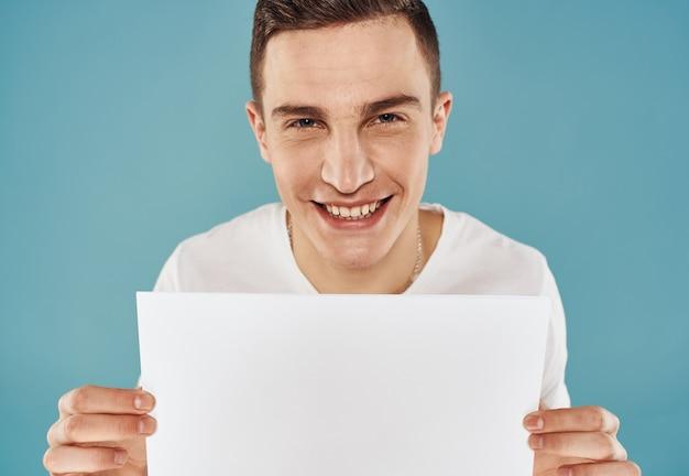 Kerl mit flyer in der hand poster modell blauen hintergrund beschnittene ansicht. hochwertiges foto