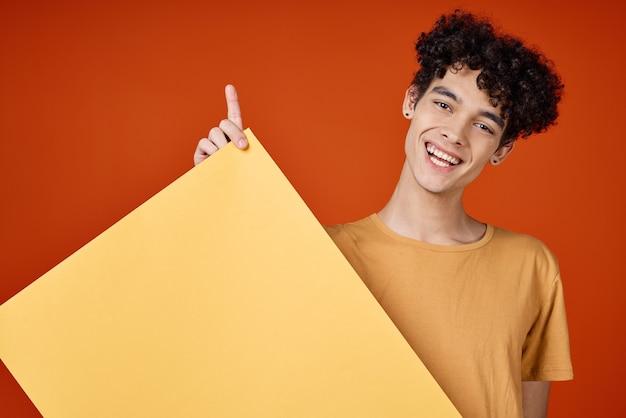 Kerl mit gelbem gelbem plakat des lockigen haares im handstudio-werbekopienraum