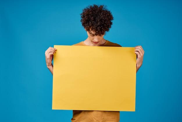 Kerl mit gelbem plakat in den händen