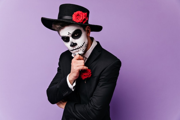 Kerl mit gemaltem gesicht für maskerade berührt nachdenklich sein kinn und schaut ernsthaft in die kamera.