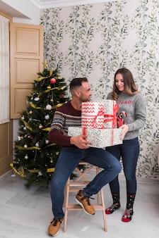 Kerl mit haufen von geschenken auf stuhl und attraktive dame in der nähe von weihnachtsbaum
