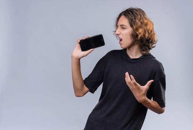 Kerl mit langen haaren im schwarzen t-shirt sprechen am telefon durch lautsprecher an weißer wand