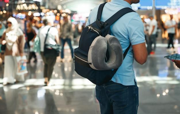 Kerl mit rucksack im flughafen nahe flugplan am flughafen