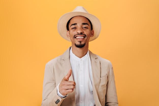 Kerl mit stylischem hut und beiger jacke lächelt und zeigt seinen finger in die kamera