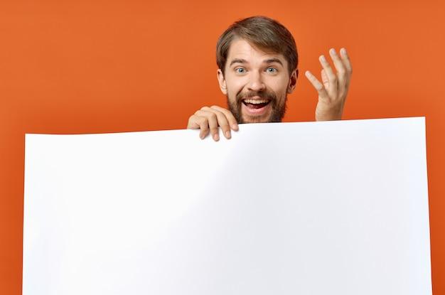 Kerl mit weißem papier auf orangefarbenem plakatmodell-werbeschild
