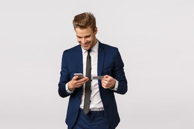 Kerl möchten blumen für freundin kaufen, das büro bearbeiten und smartphone und kreditkarte halten und lächelnde anzeige tragen die rechnungsdetailanzeige ein und stehen weißen hintergrund. geschäftsmann, der für kauf zahlt