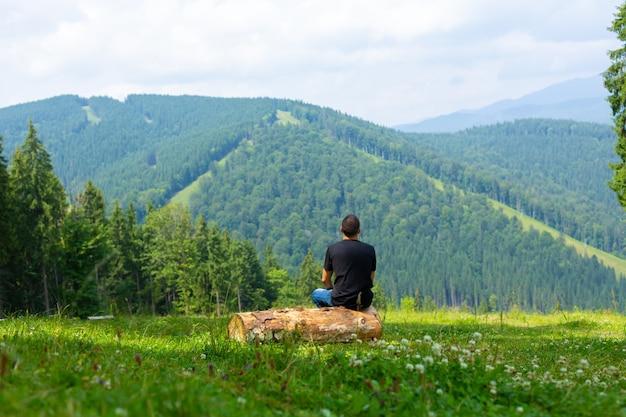 Kerl sitzt auf baumstamm und genießt friedliche grüne gebirgslandschaft