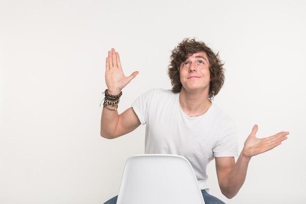 Kerl sitzt auf einem stuhl und träumt mit erhobenen händen