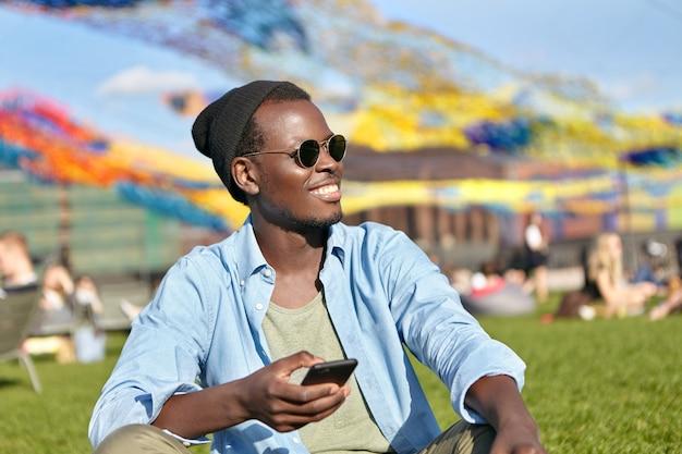 Kerl sitzt im grünen gras beim durchsuchen des newsfeeds am telefon