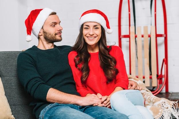 Kerl und dame in den partyhüten, die auf sofa umarmen
