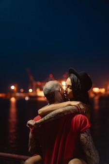 Kerl und mädchen, die auf einem hintergrund des nachthafens sich umarmen