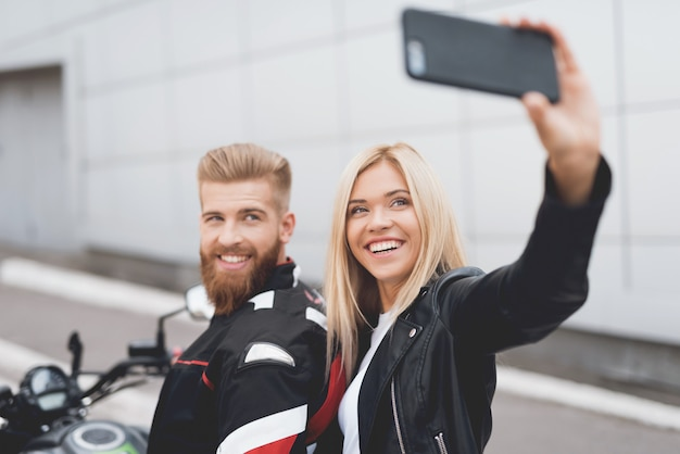 Kerl und mädchen, die das selfie, sitzend auf einem elektrischen motorrad tun.