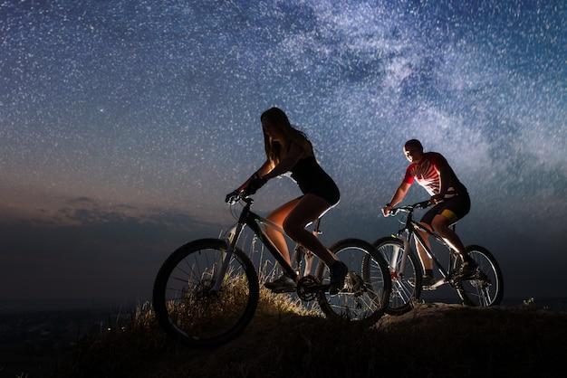 Kerl und mädchen, die fahrräder auf dem hügel nachts fahren