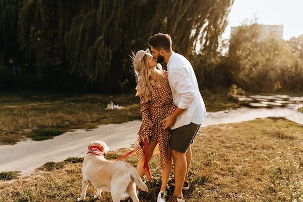 Kerl und mädchen küssen vor dem hintergrund der weide. romantisches paar macht morgenspaziergang mit ihrem geliebten hund.