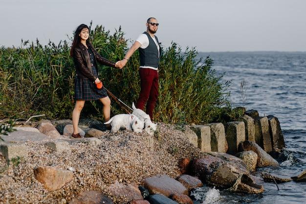 Kerl und mädchen stehen am strand mit zwei weißen welpen bei sonnenuntergang