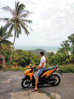 Kerltourist auf einem motorrad, das einen urlaub in thailand genießt