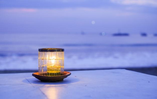 Kerze auf dem ozean bei sonnenuntergang