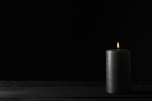Kerze auf holztisch gegen schwarz