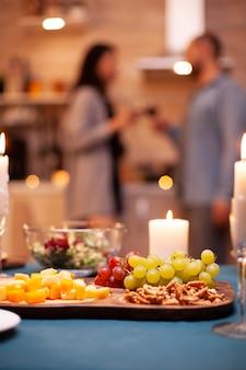 Kerze brennt auf dem tisch und nahaufnahme von trauben auf holztisch in der küche, während das paar röstet.