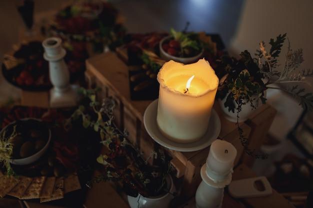 Kerze brennt auf einem tisch mit snacks