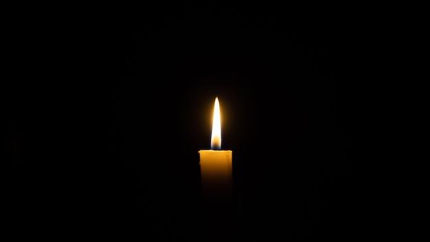 Kerze brennt im dunkelkonzept des verlustes und der erinnerung