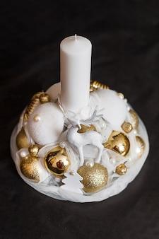 Kerze der weißen weihnacht mit golddekorationen auf schwarzem backgound.