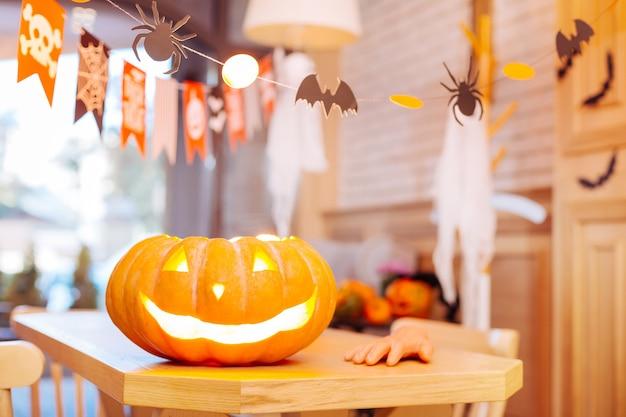 Kerze drinnen. schließen sie oben von geschnitztem halloween-kürbis mit kerze innen stehend auf feier-tisch