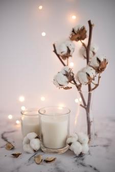 Kerze im kerzenhalter nahe baumwollzweig auf marmor mit belichtetem licht im hintergrund