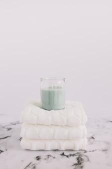 Kerze im kerzenhalter über gestapelten weißen servietten auf marmoroberfläche
