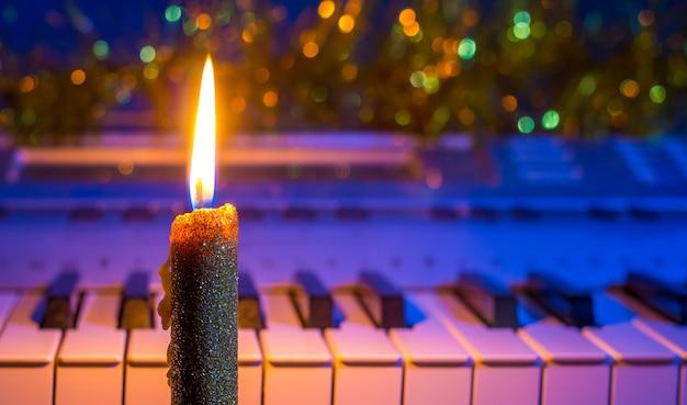 Kerze in der nähe des klaviers weihnachts- und neujahrsmusik
