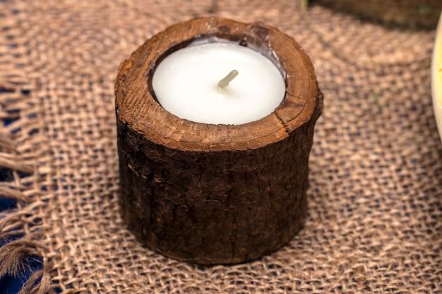 Kerze in einem hölzernen kerzenständer auf einem romantischen hintergrund.