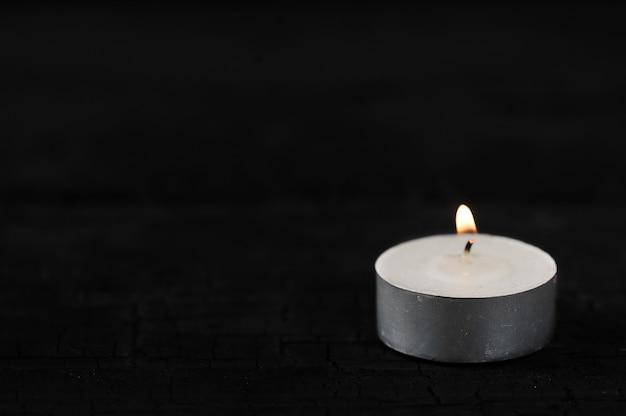 Kerze mit brennendem feuer auf schwarzem