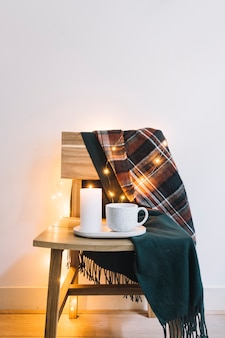 Kerze mit Cup auf Holzstuhl