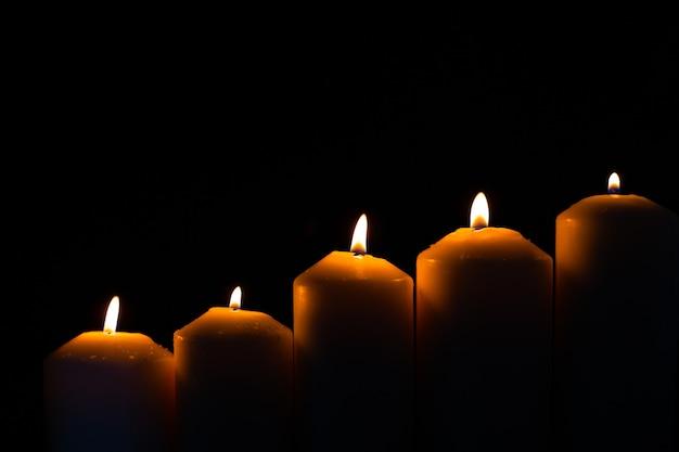 Kerze mit fünf flammen, die hell auf schwarzem hintergrund brennt