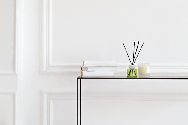 Kerze und aromatischer reederfrischer auf tabelle im badekurortsalon. aromaflüssigkeit in glasflasche mit rohrstäbchen. aroma diffusor in luxury im schlafzimmer. hygge. skandinavische wohnkultur kerzen, duft, bücher